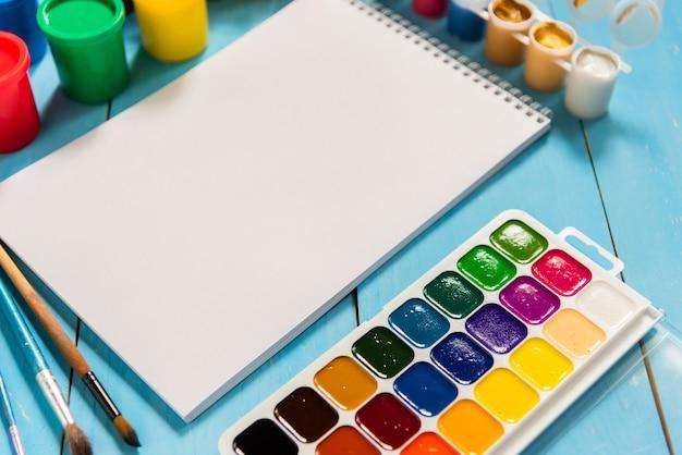 Caderno de desenho e aquarelas com guache sobre fundo azul.