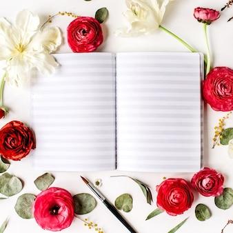 Caderno de desenho e ranúnculo de rosas vermelhas