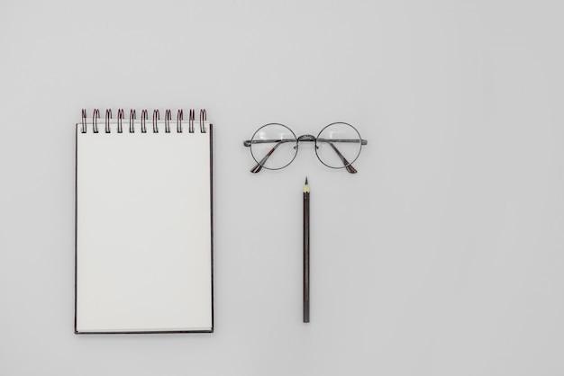 Caderno de desenho em espiral simulado acima em abstrato. óculos e lápis preto.