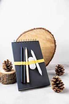 Caderno de desenho ou caderno, lápis, borracha, pinhas