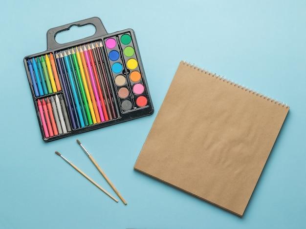 Caderno de desenho, pincéis e um conjunto de tintas e lápis sobre fundo azul.