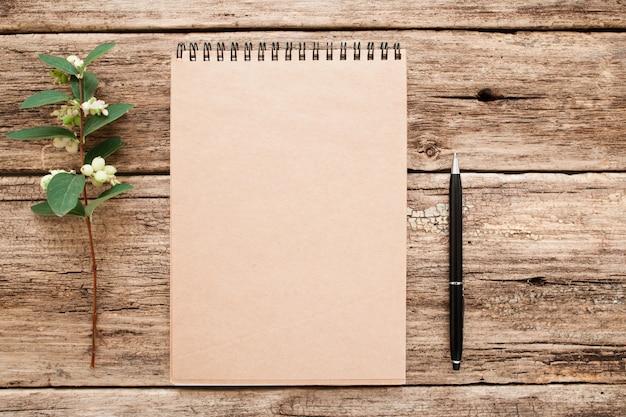 Caderno de desenho vintage com caneta e flor