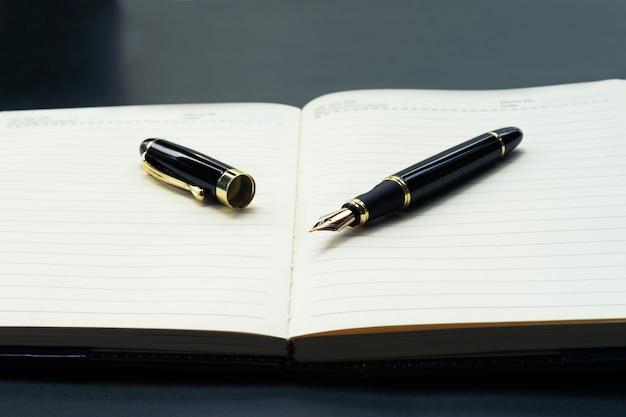 Caderno de diário forrado aberto com uma caneta de luxo com espaço de cópia