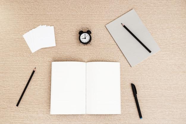Caderno de escola aberta e lápis, caneta, adesivos para anotações na mesa de madeira clara. volta ao conceito de escola. trabalhando em casa.