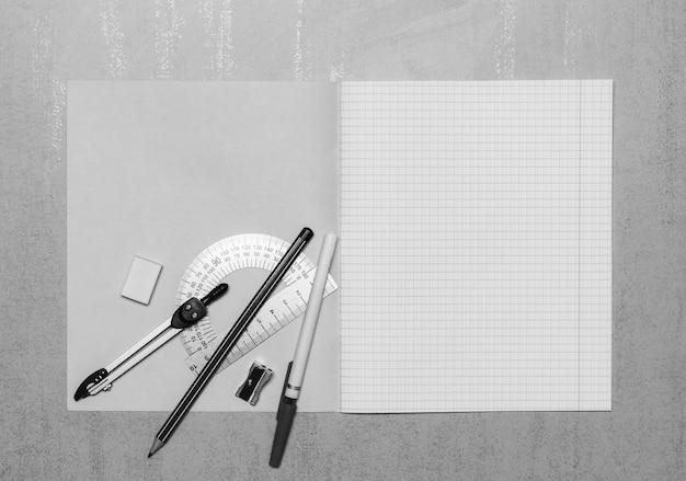 Caderno de escola aberta simulado acima com espaço de cópia, caneta esferográfica, lápis, borracha, bússolas, transferidor de aço e apontador de lápis vista superior, foto preto e branco