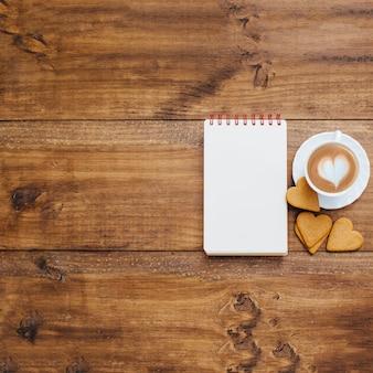 Caderno de escola e caneca de café em um fundo de madeira