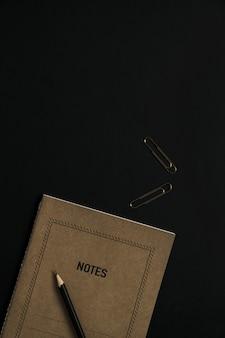 Caderno de folha de papel artesanal, lápis, clipes em preto