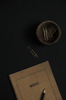 Caderno de folha de papel artesanal, lápis, clipes em uma tigela de madeira em preto
