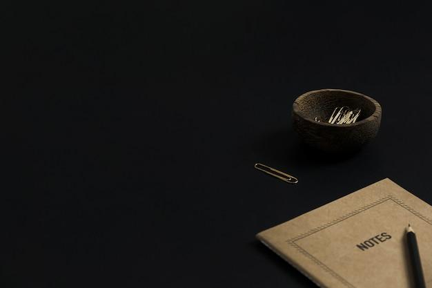 Caderno de folha de papel ofício, lápis, clipes em uma tigela de madeira em fundo preto. área de trabalho da mesa do escritório doméstico