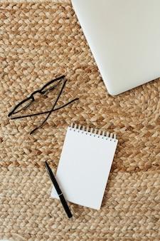 Caderno de folha em branco com espaço de cópia para texto, óculos, caneta, laptop em fundo de palha de vime