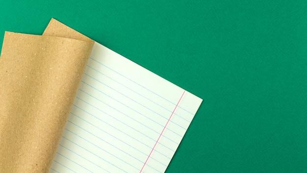Caderno de livro de exercícios na mesa verde, fundo de conceito de escola e educação com papel pautado, espaço de cópia, foto de vista superior