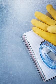 Caderno de luvas de óculos de segurança na mesa metálica, conceito de construção