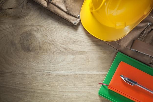 Caderno de notas caneta cinto de ferramentas de couro para construir capacete na placa de madeira
