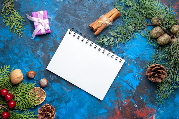 Caderno de notas de cima, cones de galhos de árvore de abeto, brinquedos de árvore de natal em fundo azul.