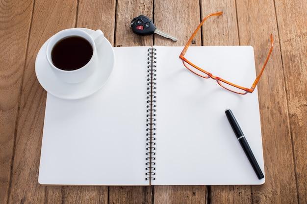 Caderno de notas vazio com xícara de café e acessórios em fundo de madeira antigo