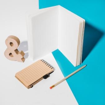 Caderno de página branca; bloco de notas em espiral; símbolo de e comercial e lápis em fundo duplo