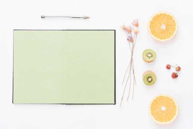 Caderno de página em branco; caneta; flor seca; morango e frutas cortadas ao meio no pano de fundo branco