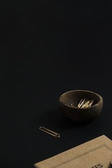 Caderno de papel artesanal, lápis, clipes em tigela de madeira em preto
