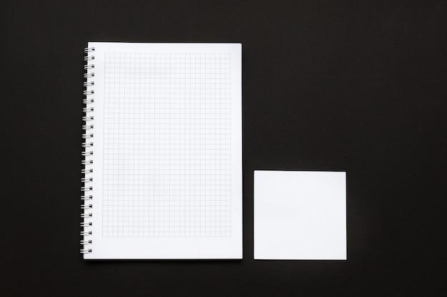 Caderno de papel branco e um pedaço de papel em uma superfície preta