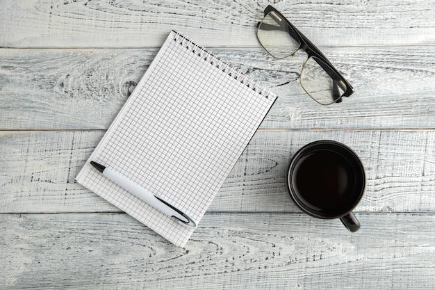 Caderno de papel, caneta e xícara de chá ou café e óculos ópticos em madeira branca gasto vintage, vista superior