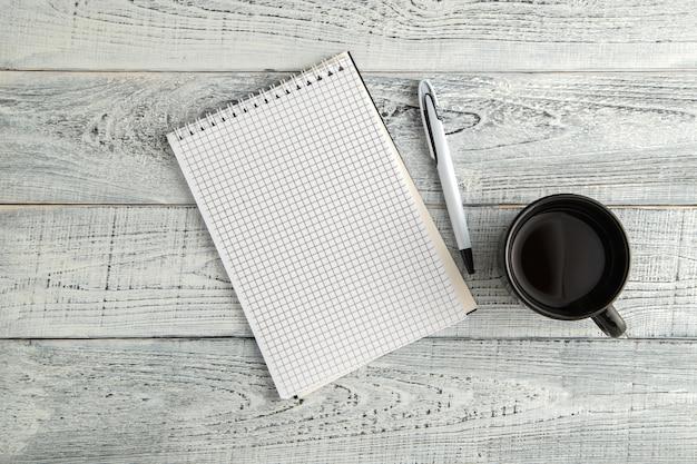 Caderno de papel, caneta e xícara de chá ou café em madeira branca gasto vintage, vista superior
