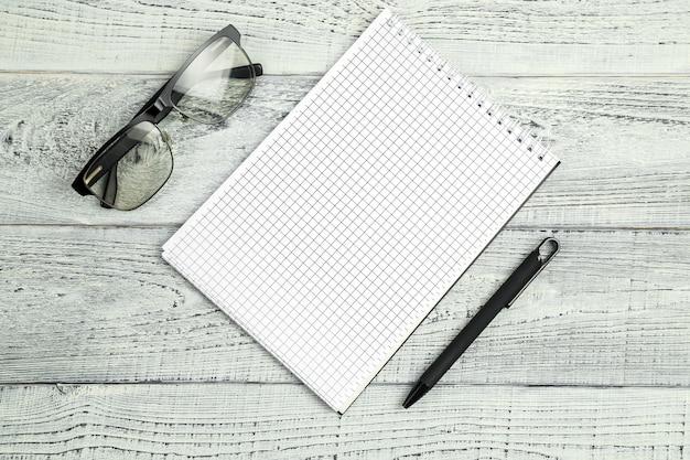 Caderno de papel com caneta esferográfica e óculos ópticos em fundo isolado de madeira