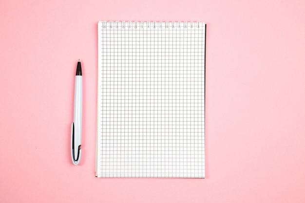 Caderno de papel com caneta no fundo rosa isolado. vista do topo. configuração plana. brincar