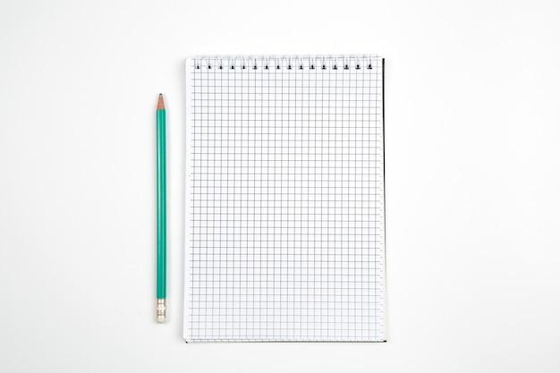 Caderno de papel com caneta ou lápis em fundo branco isolado. vista do topo. configuração plana. brincar