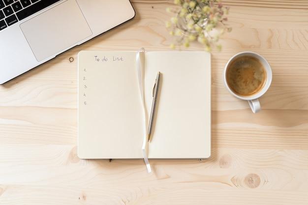 Caderno de papel em branco de vista superior com lista de tarefas, flores, teclado de laptop, xícara de café e caneta.