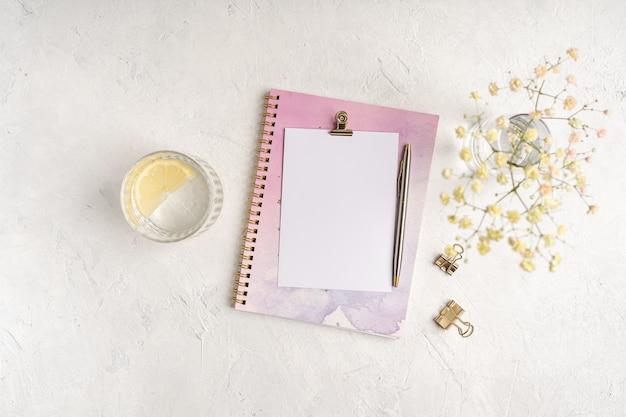 Caderno de papel em branco de vista superior, flores, clipes de pasta de papel dourado, água com limão e caneta. postura plana