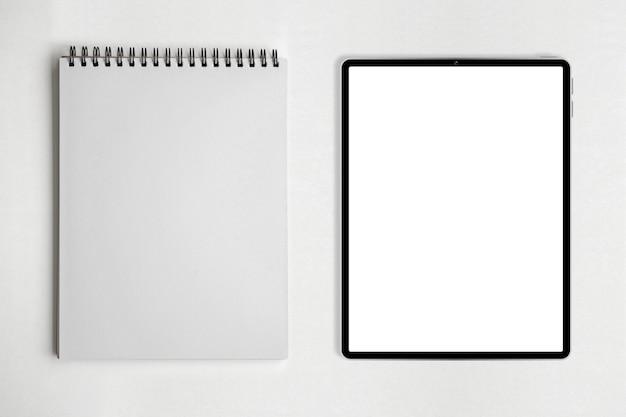 Caderno de papel em branco ou bloco de notas e tablet na mesa branca.