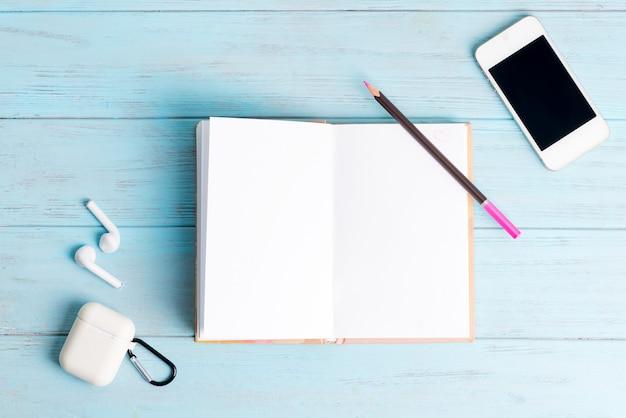 Caderno de papel para anotações, smartphone moderno e fones de ouvido