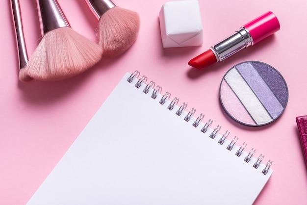Caderno de papel plano deitado na mesa de cosméticos rosa