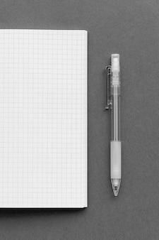 Caderno de papel quadriculado em branco com um lápis