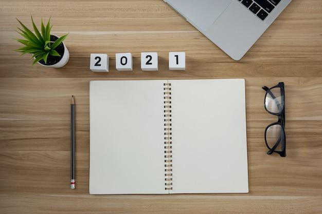 Caderno de papel vazio com fofo do ano número 2021 para escrever o planejamento no fundo da mesa de madeira
