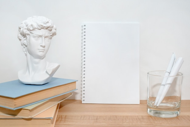 Caderno de papel vazio na mesa de madeira com livros e pequena escultura de busto de david