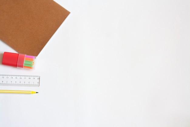 Caderno de papelaria, contadores, régua e lápis, espaço de cópia