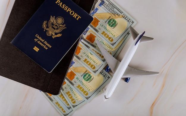 Caderno de planejamento com passaporte americano de avião, férias, notas de dólar, férias de avião