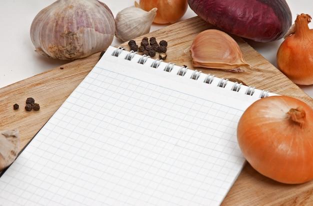 Caderno de receitas culinárias em uma placa de corte
