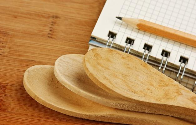 Caderno de receitas culinárias em uma tábua de cozinha Foto Premium