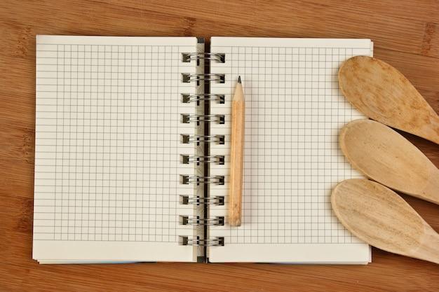 Caderno de receitas culinárias em uma tábua de cozinha