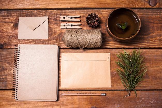 Caderno de receitas, envelopess de papel, corda e prendedores de roupa na mesa de madeira.