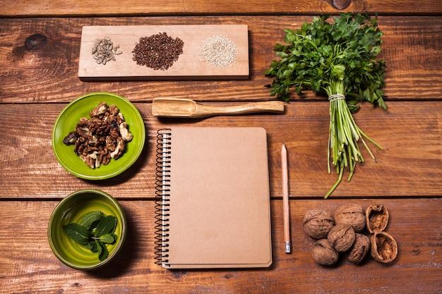 Caderno de receitas, nozes, salsa e sementes na mesa de madeira.