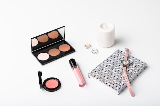 Caderno de relógio de pulso de cosméticos decorativos e vela sobre a superfície branca