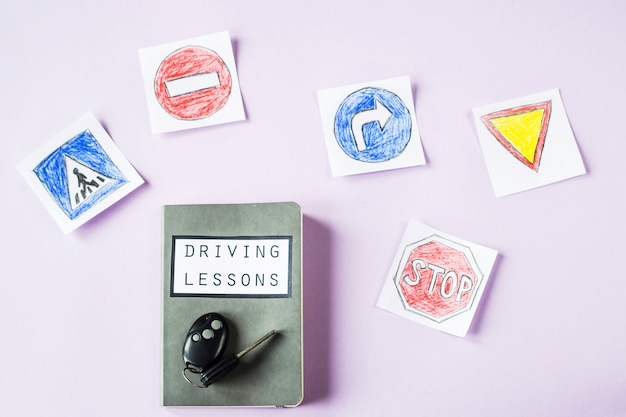 Caderno de treino para aulas de condução e regras de trânsito ao lado dos desenhos de sinalização para obter uma carta de condução
