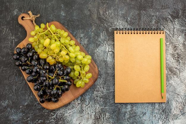Caderno de uvas com vista superior, cachos de uvas verdes e pretas na tábua