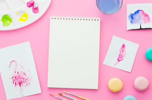 Caderno de vista superior com aquarela e macarons