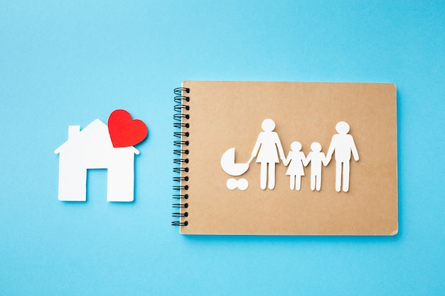 Caderno de vista superior com figura de família e casa
