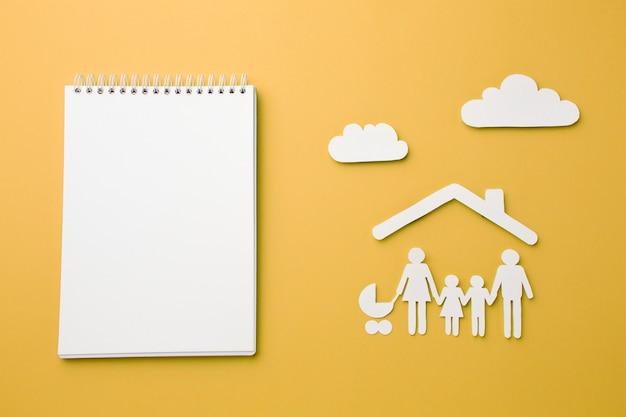 Caderno de vista superior com figura de família e nuvens