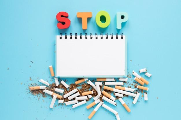 Caderno de vista superior com palavra colorida e cigarros